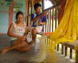 "Amazon artisan Felicita Butuna Chichaco and son Bill Panduro making chambira palm fiber ""naca naca"" snake model belt in Brillo Nuevo, Peru - Photo by Campbell Plowden/CACE"