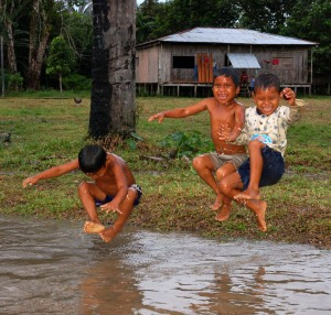 Boys jumping into puddle at Bora village of Brillo Nuevo. Photo by Campbell Plowden/CACE