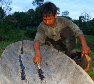 Bora woodsman caulking canoe wih copal resin. Photo by Campbell Plowden/CACE