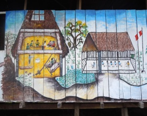 `Painting of traditional Huitoto scene on modern house