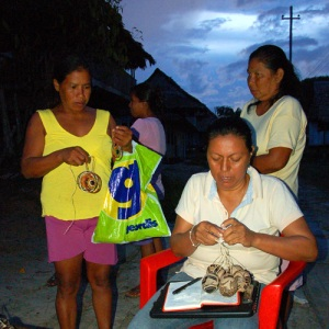 Yully Rojas receiving crafts from Huitoto artisans at Puca Urquillo