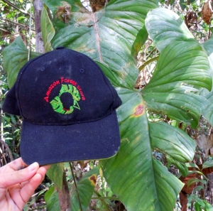 Amazon Forest Store hat next to jungle leaf. Photo by C. Plowden/CACE