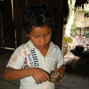 Ocaina boy feeding pet pigeon. Photo by C. Plowden/CACE
