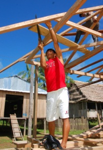 Bora man sawing beam building community pharmacy at Brillo Nuevo. Photo by C. Plowden/CACE