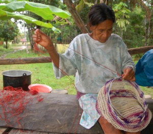 Ocaina native artisan Rosa weaving chambira palm fiber bag in Nueva Esperanza, Peru. Photo by Campbell Plowden/Center for Amazon Community Ecology