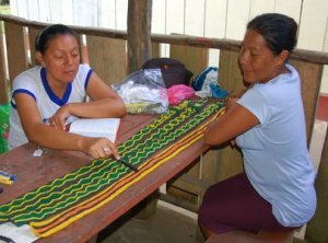 CACE project manager reviewing guitar straps with Bora artisan. © Photo by Campbell Plowden/Center for Amazon Community Ecology