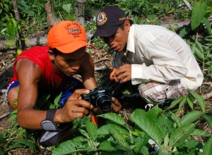 Bora men photographing insect at Brillo Nuevo. Photo by Campbell Plowden/Center for Amazon Community Ecology