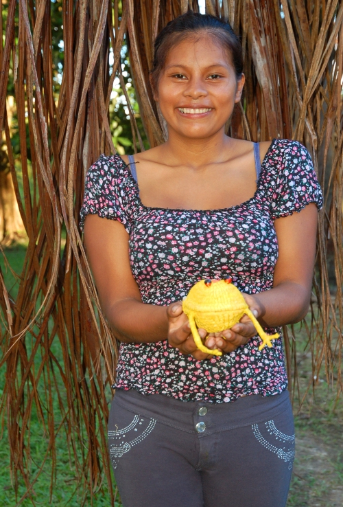Dina Peña with yellow frog. Photo by Campbell Plowden/Center for Amazon Community Ecology