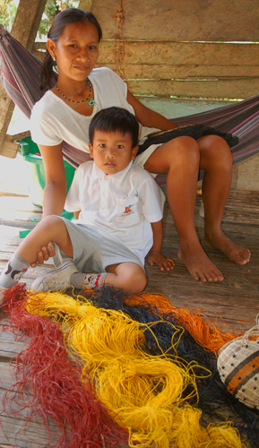 Bora artisan and son with chambira fiber basket dyed with guisador root and other plants at Puca Urquillo. Photo by Campbell Plowden/Center for Amazon Community Ecology