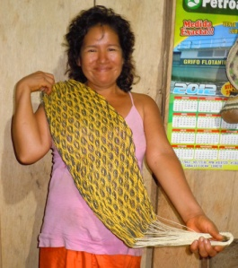 Yagua artisan from San Jose de Piri with woven chambira fiber doll's hammock dyed with guisador root and other plants. Photo by Campbell Plowden/Center for Amazon Community Ecology