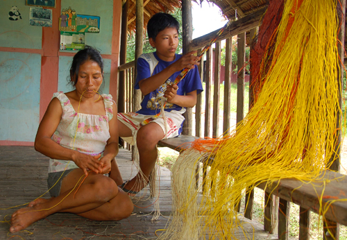 Bora artisan and son weaving chambira fiber belts dyed with guisador root and other plants at Brillo Nuevo. Photo by Campbell Plowden/Center for Amazon Community Ecology