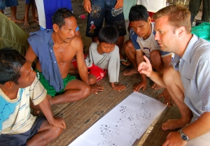 Michael Gilmore discussing map with Maijuna in Nueva Vida (2009).  Photo by Campbell Plowden/Center for Amazon Community Ecology