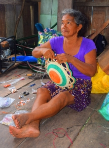 Romelia sewing in new beads to basket. Photo by Campbell Plowden/CACE